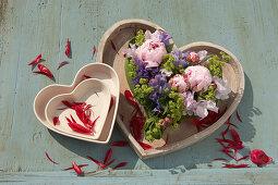 Sweet peas, peonies and ladies' mantle arranged in floral foam in heart-shaped bowl