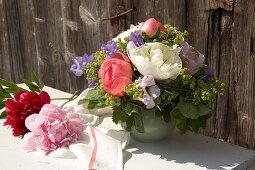 Spring bouquet of peonies, ladies' mantle and sweet peas