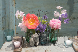 Peonies and sweet peas in bottles in bottle holder decorating table