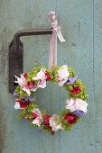 Wreath of peonies, sweet peas and ladies' mantel hung from vintage door handle