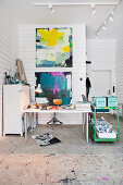 Desk and green, vintage serving trolley in artist's studio with paintings on white wooden wall