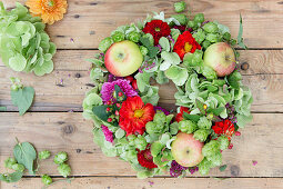 Late-summer wreath of hops, green hydrangeas, zinnias and apples