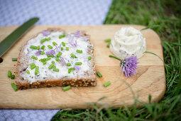 Brot mit selbst gemachter Schnittlauchhblütenbutter und Schnittlauch