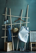 DIY coat rack made from wooden poles and butchers' hooks against green-grey wall