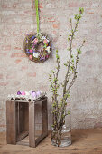 Spring flowers on floor case below flower wreath on wall