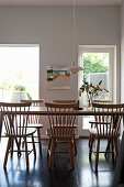 Spoke-back chairs around wooden table in dining room with garden access