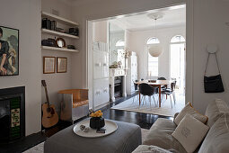 Living room in shades of grey with open doorway leading into dining room in period building