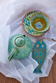 Ceramic teapot, dishes and fish ornaments glazed in shades of turquoise