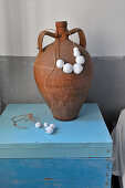 Bead necklace around clay amphora on light blue wooden box