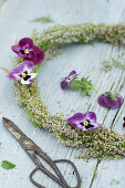 Wreath of heather decorated with purple violas and scissors