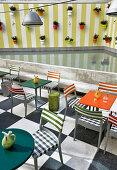 Stühle und Bistrotische in einem Restaurant auf Dachterrasse, Blumentöpfe an der Wand