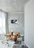 Baumstamm-Hocker in verschiedenen Formen und Stehleuchte im Zimmer mit grauen Wänden