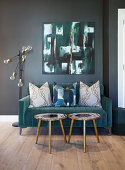 Turquoise velvet sofa with scatter cushions and small side tables below abstract painting on wall