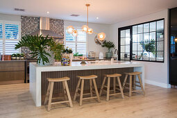 Wooden stools at long, glossy, white island counter in kitchen