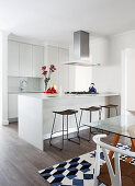 Island counter and bar stools in white, open-plan kitchen with glass table in dining area