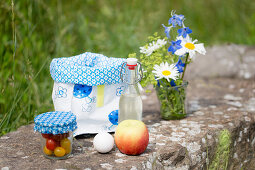 Posy in glass, oilcloth lunch bag, swing-top bottle, apple, egg and jar of tomatoes for picnic