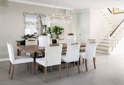 Table, chairs with pale upholstery and Venetian mirrors on wall in elegant dining room