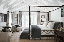 Four-poster bed, loose-covered armchairs and round table in country-house bedroom with exposed wooden roof structure