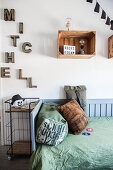 Bed, metal shelving, old wine crates used as shelving modules and name made of decorative letters in teenager's bedroom