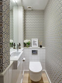 Narrow guest toilet with patterned wallpaper