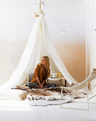 Frau sitzt unterm hängenden Zelt mit Fellen und Couchtisch