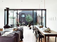 Offener Wohnraum mit offener Fensterfront zur Terrasse