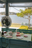 Set table on summery veranda with sea view