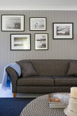 Bildergalerie mit Schwarz-Weiß-Fotos überm grauen Sofa