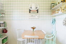 Dining area in bright kitchen with white wainscoting and green-and-white wallpaper