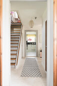 Pale wooden floor and staircase in hallway with view into kitchen at far end