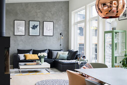 Black leather couch and coffee table next to window and grey mottled wall in open-plan interior