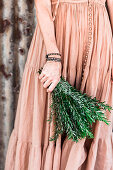 Woman in nostalgic dress holds a bunch of rosemary sprigs in her hand