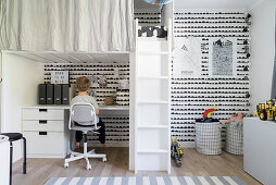Loft bed above desk in child's bedroom with black-and-white wall; boy seated at desk