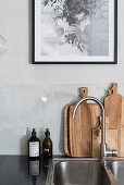 Sink and chopping boards below picture in kitchen