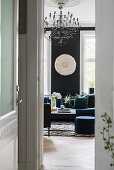 View through open door into elegant living room with black wall and black and white accessories
