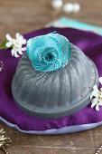 Turquoise fabric flowers on small bundt-cake tin