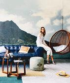 Blaue Ledercouch und Hängesessel im Wohnzimmer mit Postertapete, junge Frau auf Couch sitzend