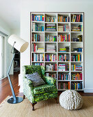 Antique armchair with green cover, pouf and floor lamp in front of bookshelf