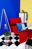Hand legt Sonnenbrille auf roten Designeresssel vor blauer Wand