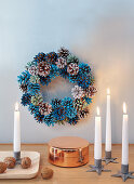 Candles in front of a wreath made from painted pine cones