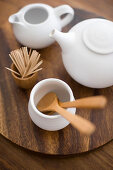 Wooden cutlery, toothpicks and white teapots on wooden table