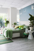 Bed line in shades of green on white double bed with headboard in open-plan bedroom