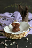 Chocolate Easter bunny in small hand-made ceramic dish on raffia nest