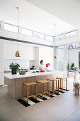 Woman and dog in modern open kitchen with high ceiling