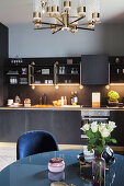 View across dining table to black kitchen counter with gold details