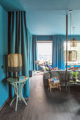 Long curtains in petrol-blue living room
