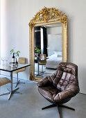 Bistrotisch mit Stühlen Wandspiegel mit verziertem Goldrahmen und Ledersessel
