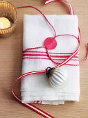 Cloth napkin wrapped and decorated with gift ribbon and bauble