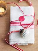 Stoffserviette umwickelt und dekoriert mit Geschenkband und Christbaumkugel
