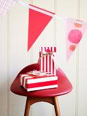 Geschenkpäckchen in rot-weiss gestreiftem Geschenkpapier auf Hocker